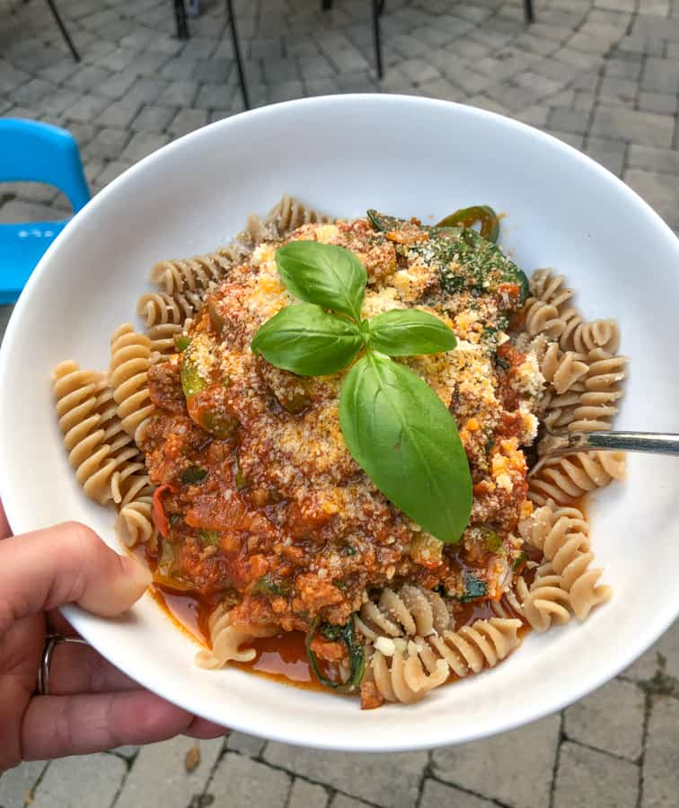 homemade pasta with meat and veggie sauce and fresh basil