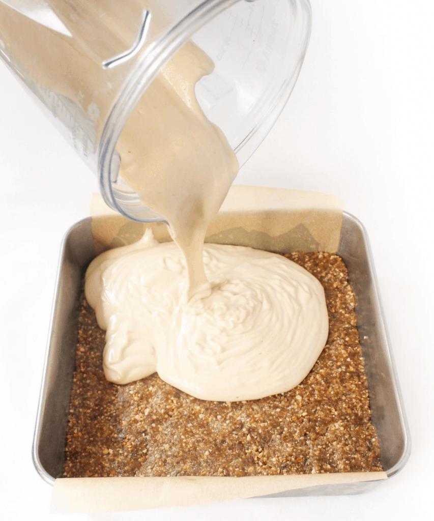 pouring lemon bars mixture over no bake crust in pan