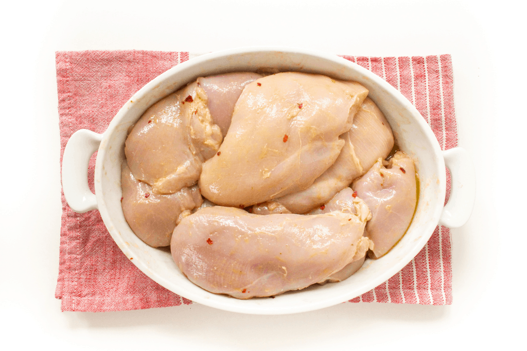 chicken and marinade in a white dish