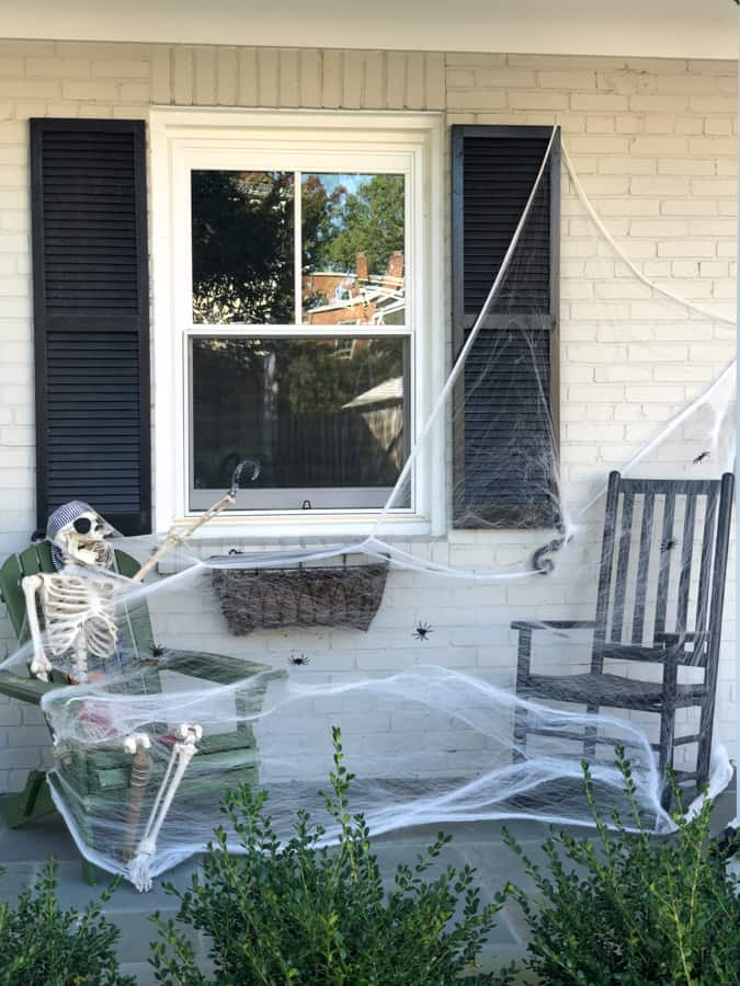 halloween decoration skeleton with cobwebs in a rocking chair