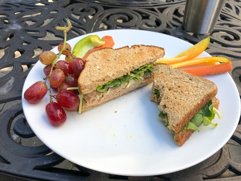 tuna salad sandwich with grapes, carrots, and bell pepper