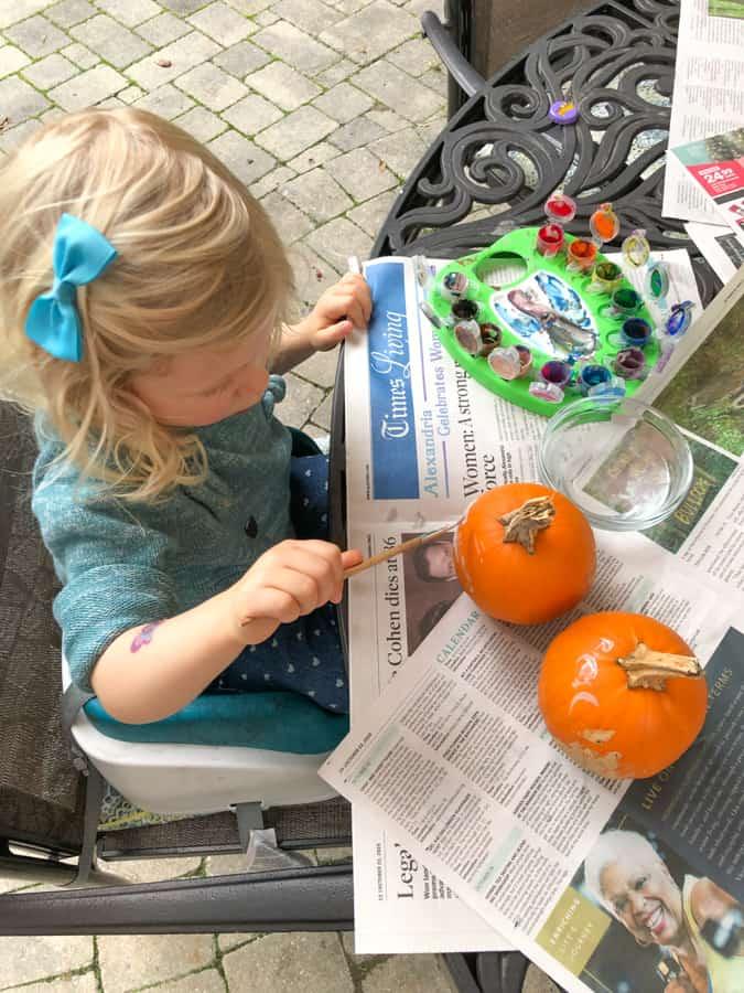 toddler painting mini pumpkins