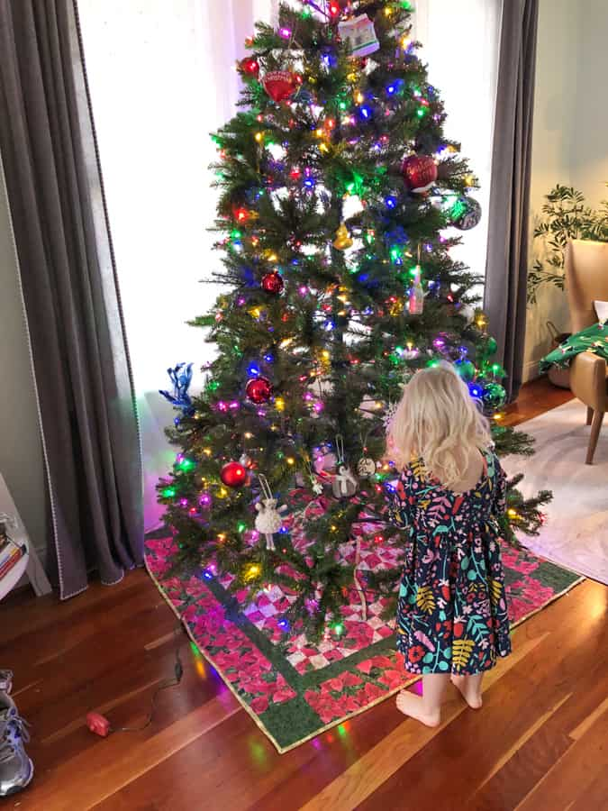 toddler helping decorate christmas tree