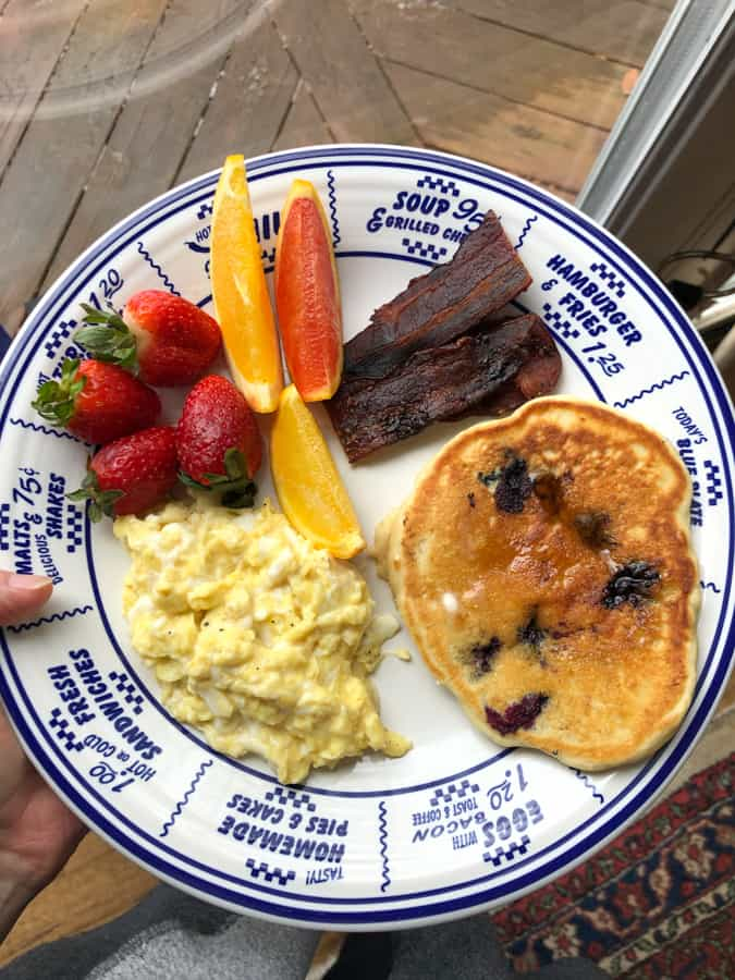 sourdough pancakes with scrambled eggs, bacon and fruit
