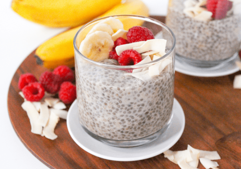 chia pudding in a glass jar with sliced bananas, raspberries, and flaked coconut sprinkled on top