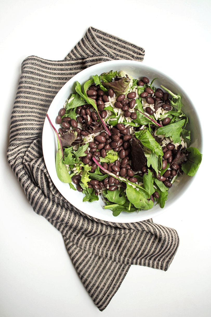 mexican salad bowl base: large bowl with greens and black beans