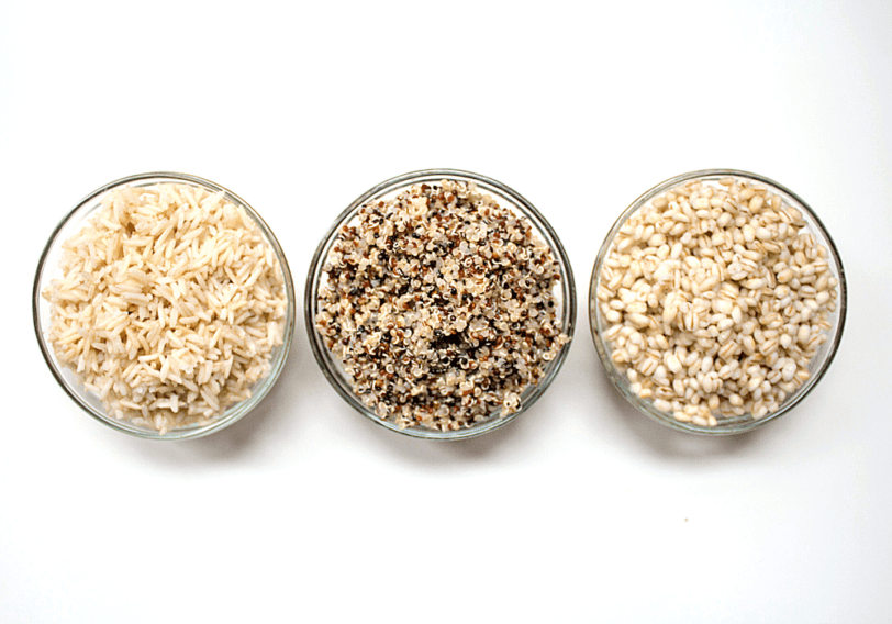 cooked brown rice, quinoa, and barley in small glass bowls