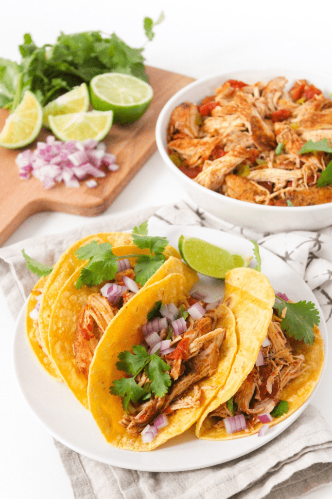 shredded chicken tacos with sliced limes and red onions in the background