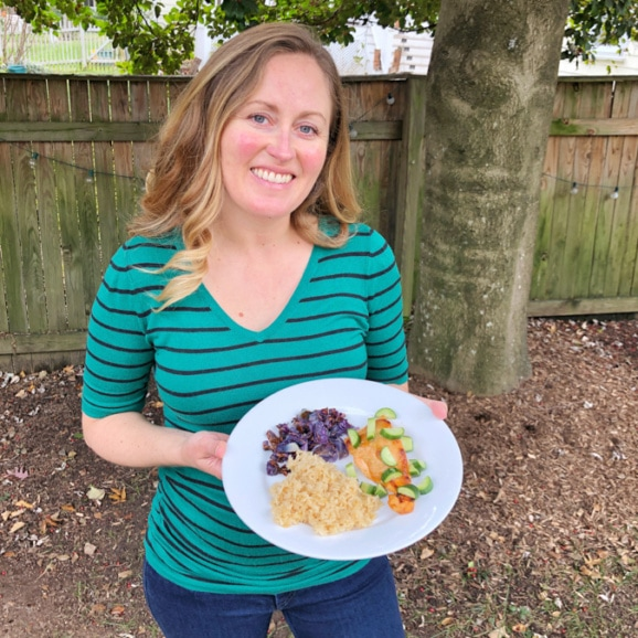 anne holding plate of blue apron salmon
