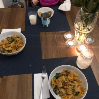 kale and sausage rigatoni dinner with candles