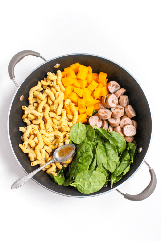sage butter pasta with chicken sausage in a large skillet
