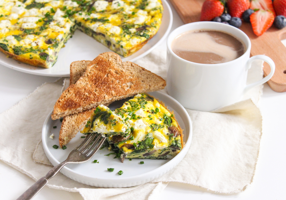 slice of goat cheese frittata on a white place with slices of toast and a coffee cup beside it