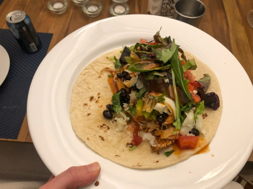 burrito filled with mexican chicken, cheese, black beans, cilantro, tomato, and lettuce