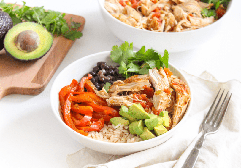 Instant Pot mexican chicken in a white bowl with avocados in the background