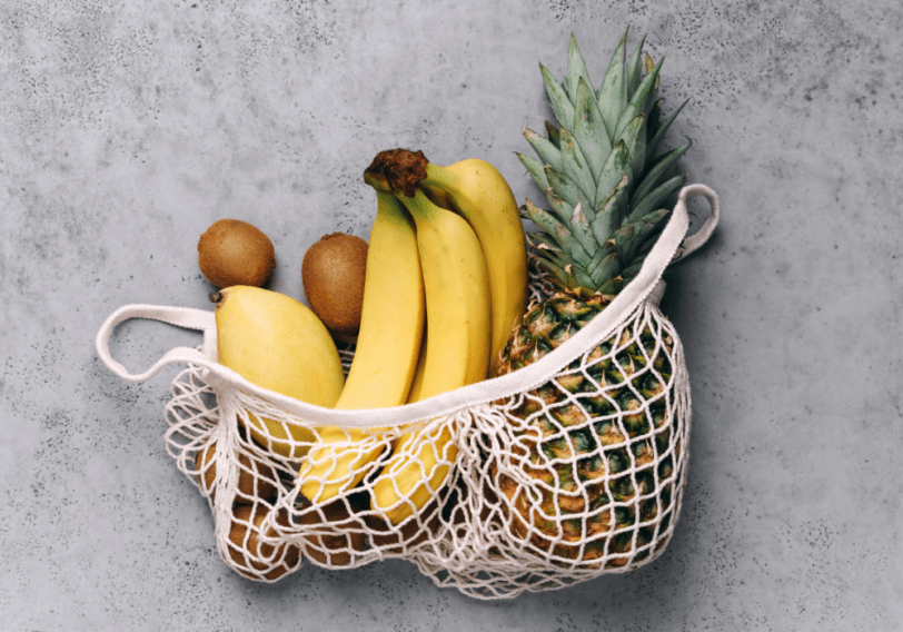 mango, pineapple, and bananas in a mesh shopping bag