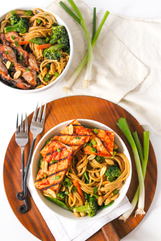 peanut butter noodles with veggies and bbq tofu in a bowl