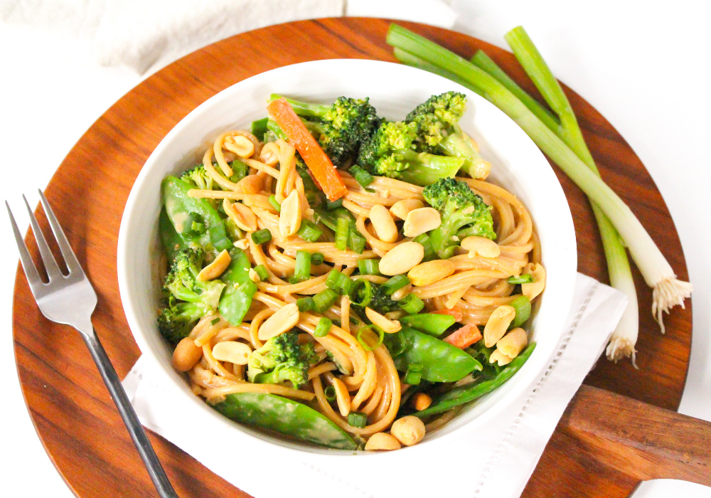 veggie pasta with peanut sauce in a white bowl on a wooden platter