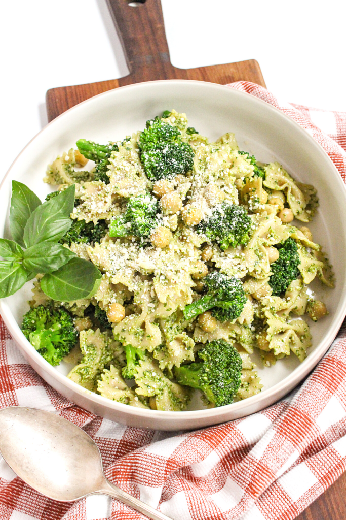 pesto pasta with broccoli and chickpeas in a white bowl on a checkered towel