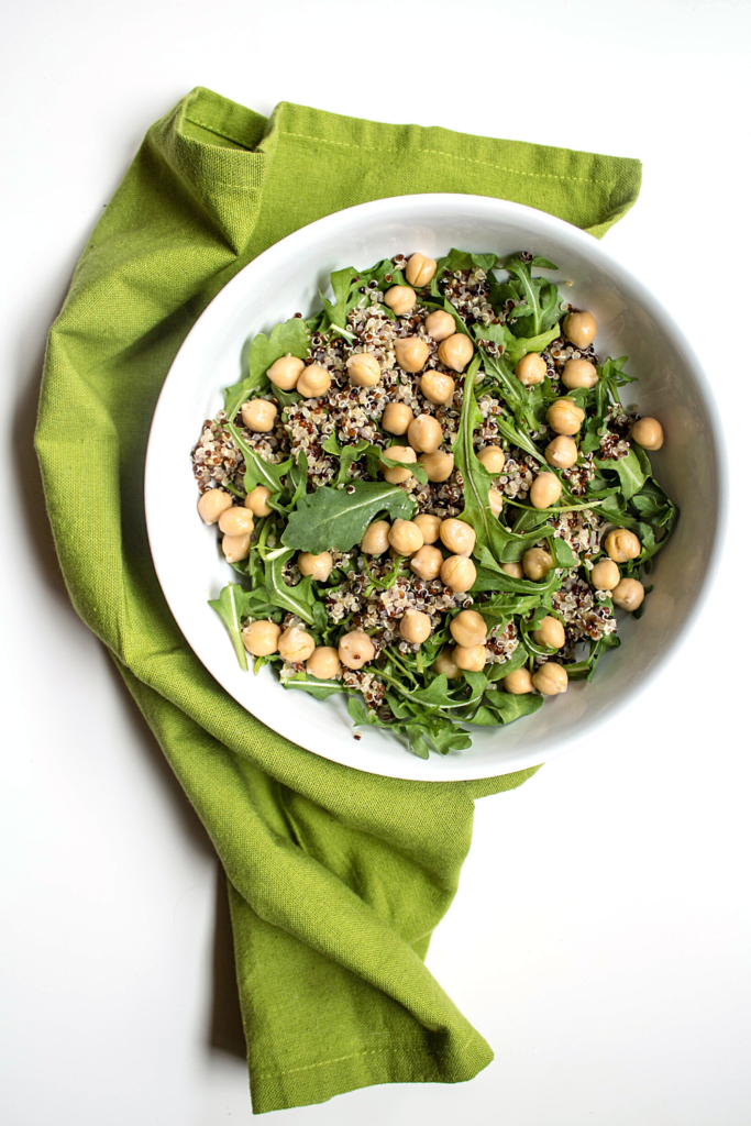 chickpeas and quinoa in a salad bowl with greens