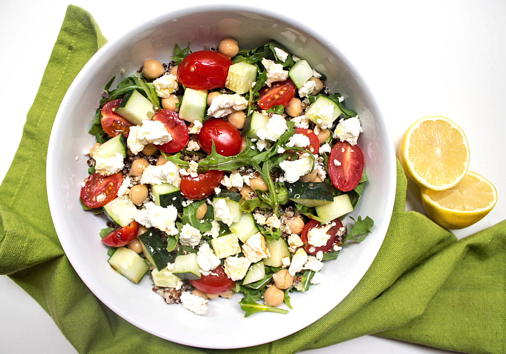 quinoa chickpea salad with feta in a white bowl with sliced lemons