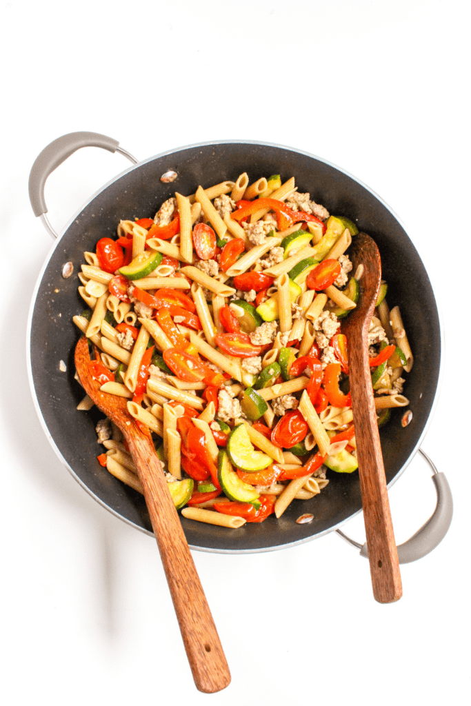 ground turkey penne pasta with vegetables in a skillet