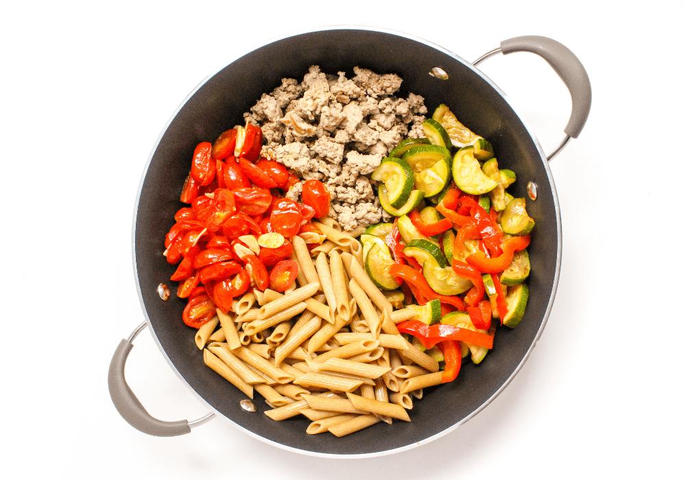 penne pasta ingredients in a large skillet