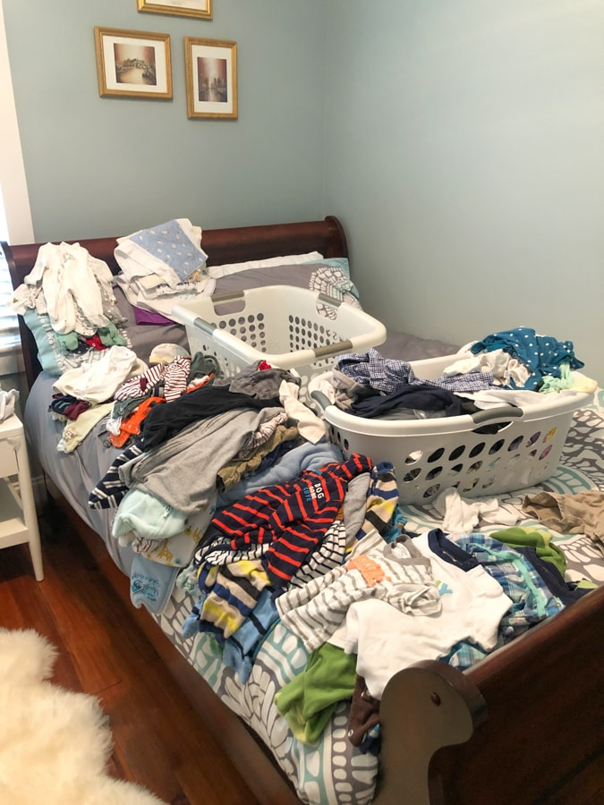 bed covered with baby boy clothes