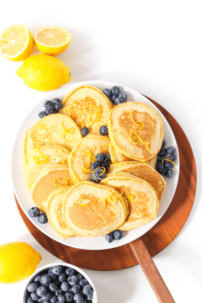lemon pancakes with ricotta spread out on a plate, with lemon slices and a bowl of blueberries beside it