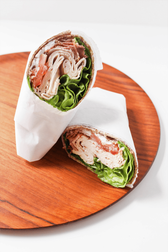turkey club wrap with bacon on a wooden platter