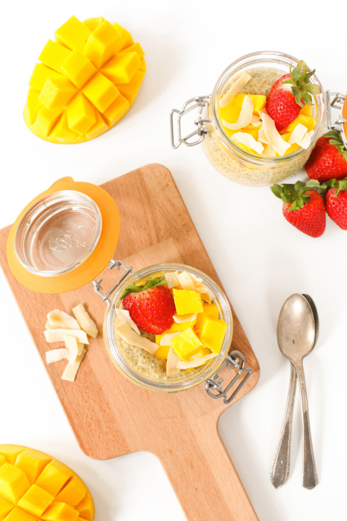 flat lay of mango chia pudding with coconut and strawberries