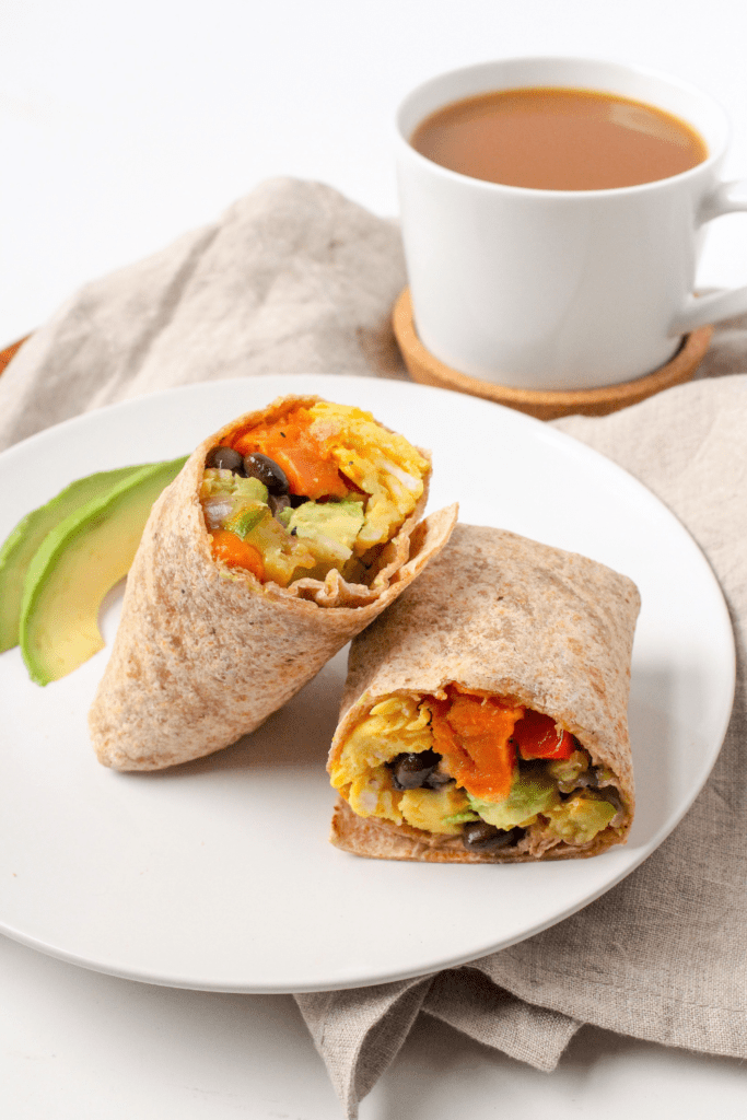 vegetarian breakfast burritos with sweet potato on a plate with a mug of coffee in the background