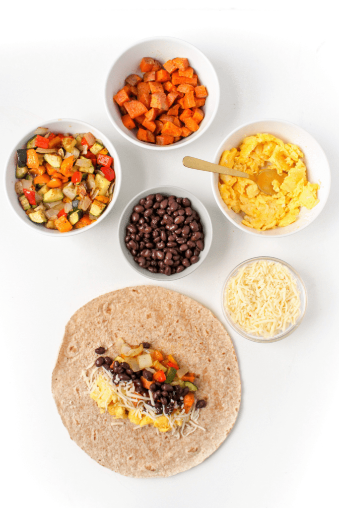 vegetarian breakfast burritos ingredients in small bowls next to a large tortilla