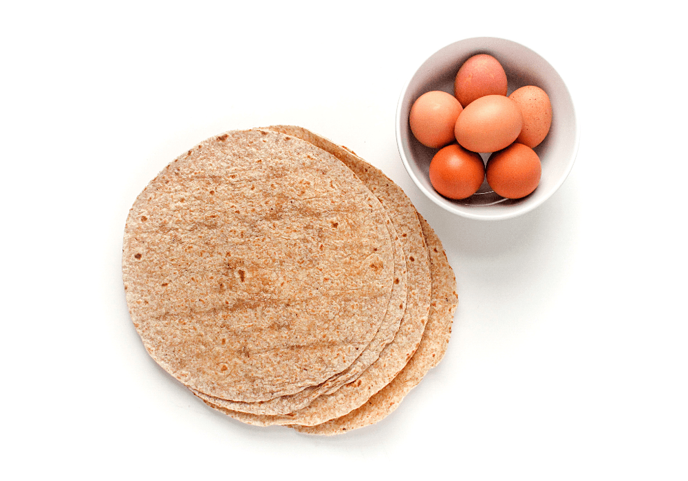 breakfast burrito ingredients: a stack of tortillas next to a bowl of eggs