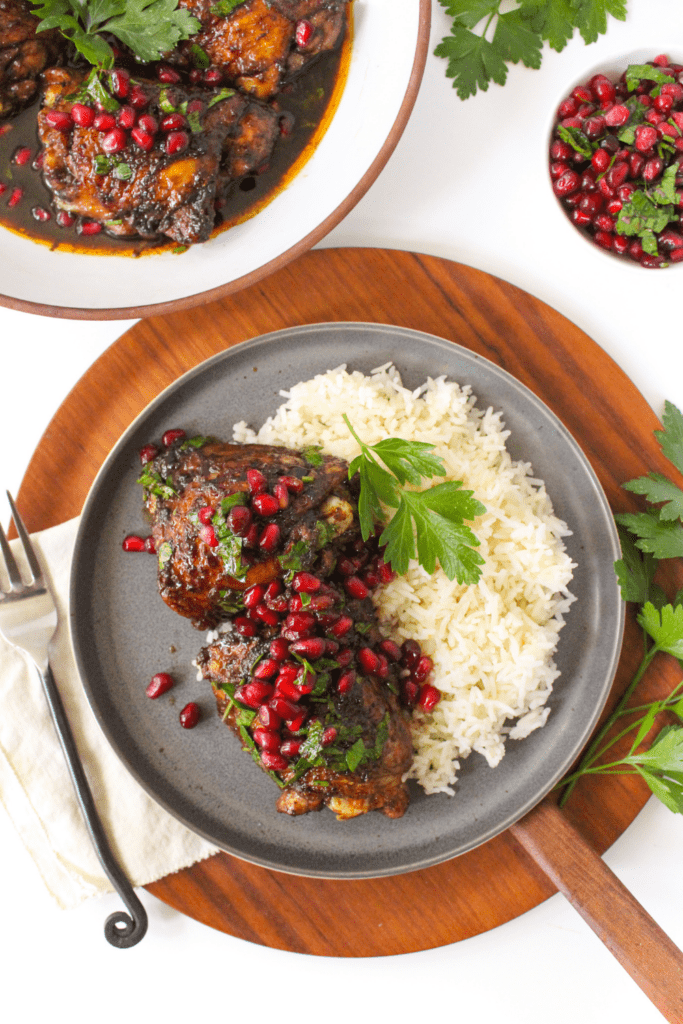 pan seared chicken thighs with pomegranate seeds and rice on a plate