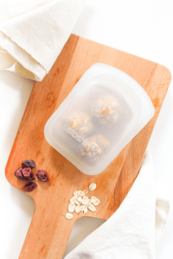 peanut butter bliss balls in a plastic storage container