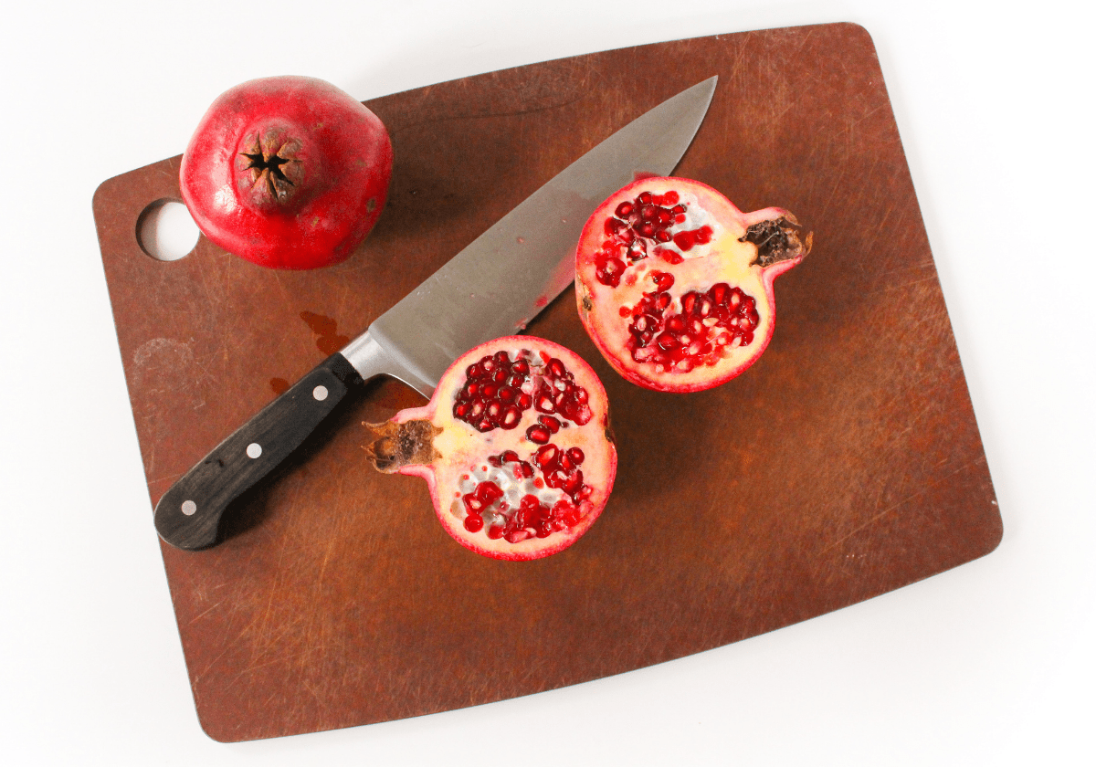 sliced pomegranate on a wooden cutting board with a knife